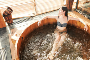 Relief after hard working stressful day. Beautiful woman, feels pleased, lying in warm whirlpool, rests in health and spa centre, enjoys calm atmosphere.