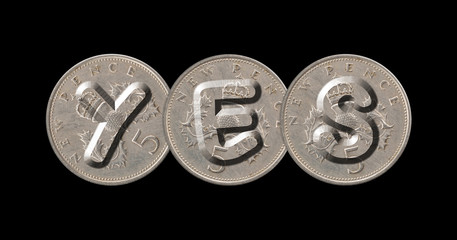YES written with old British coins on black background