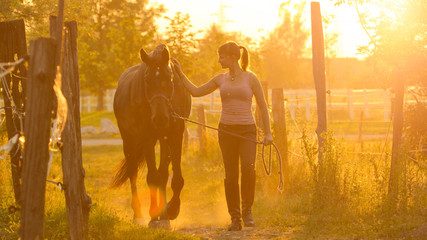 SUN FLARE: Cheerful girl walking down the grassy trail with her beautiful horse.
