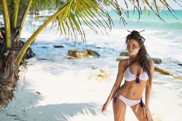 Young sexy woman is wearing bikini  posing in the shadow of a palm tree