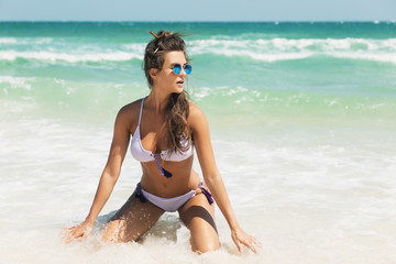 Sexy woman on the beach of the beautiful blue sea
