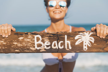 Happy wearing swimsuit with old wooden sign on the beach