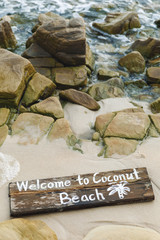 Wooden sign with lettering on the beach