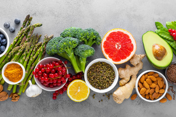 Healthy food background, spinach, quinoa, apple, blueberry, asparagus, turmeric, red currant, broccoli, mung bean, walnuts, grapefruit, ginger, avocado, almond, lemon, green peas and goji, top view