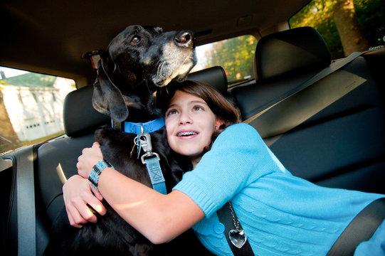 Teen girl hugs her dog