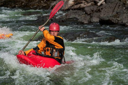 Man whitewater kayaks