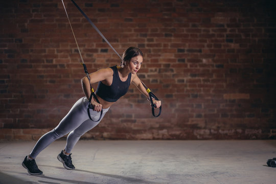 Fitness woman trainin on the TRX in the gym, doing push ups where stabilizing muscles are trained and the whole body is working, which makes such workouts truly functional.