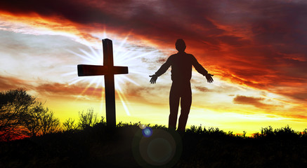 Silhouette of man and cross at sunset