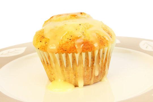 Creamy lemon sauce cascading over golden brown lemon poppy seed muffin.