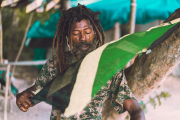 African American bearded male with dreadlocks holding Jamaica flag near tree