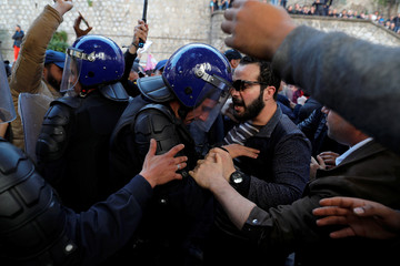 Police officers try to disperse people trying to reach the government palace during a protest against President Abdelaziz Bouteflika's plan to extend his 20-year rule by seeking a fifth term in April elections in Algiers