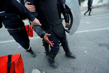 An injured anti riot-police officer is seen during clashes with people protesting against President Abdelaziz Bouteflika's plan to extend his 20-year rule by seeking a fifth term in April elections in Algiers