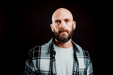 Bearded hairless hipster in shirt looking at camera on black background