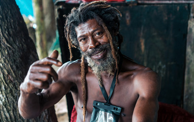 African American bearded male with dreadlocks and upped hands smoking cigar near trees