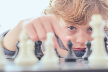 Boy holding figure on chess board