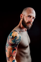 Side view of shirtless bald serious hipster with tattoos on hands looking at camera on black background