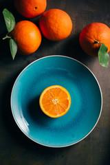 Fresh orange in a teal plate on dark background