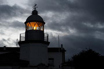 Shining lighthouse against cloudy sky