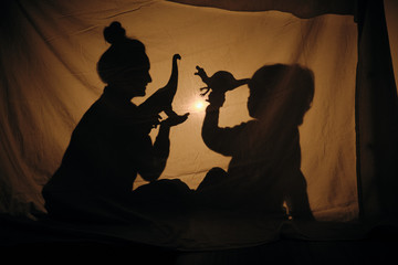 Silhouette of woman with kid playing behind sheet