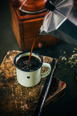 Poring hot coffee in an enamel cup with steam on dark mood