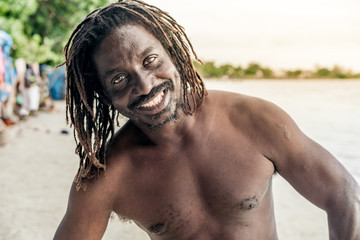 Cheerful shirtless African American male looking at camera on blurred background in Jamaica