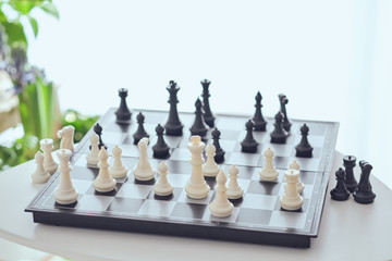 From above chess board with white and black figures on table on blurred background