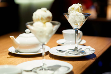 ice-cream in bowl and white dishes on the table