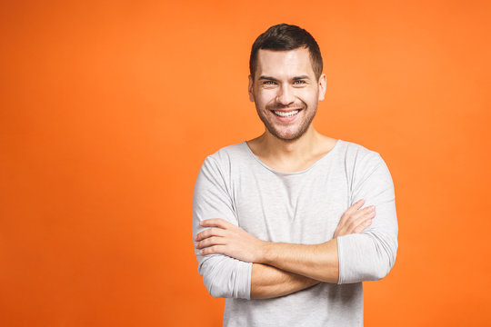 Casually handsome. Confident young handsome man keeping arms crossed and smiling while standing against orange background.