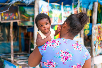 Back view of African American mother holding little kid near small souvenir shop in Jamaica