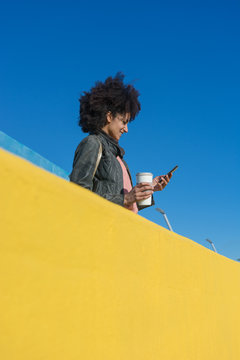 Black woman with afro hair leaning against brightly colored walls while looking at her smartphone and having a coffee