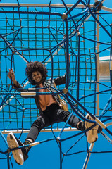 Woman with afro hair climbing by children's attractions in a park