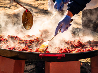 Unrecognizable person cooking traditional food called chichas on the street at a popular party in a village in Spain