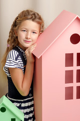 A little girl looks out from behind a toy wooden house.