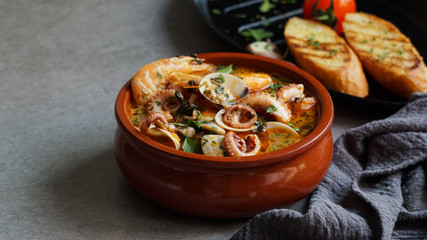 Soup of octopus and shrimps near toasts and spoon