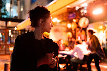 Trendy young hipster with earrings looking away near street cafe at night in Tel Aviv, Israel