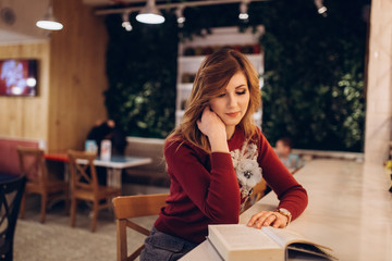 Close up portrait of young hipster modern brunette girl in cafe indoors