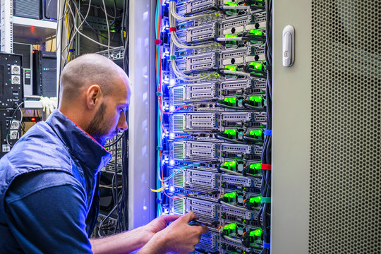 A man works with telecommunications. The technician switches the Internet cable of the powerful routers. A specialist connects the wires in the server room of the data center.