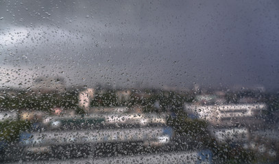 Window overlooking the spring-summer rainy city. Glass with fine drops on it. Stock background, photo