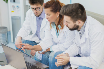 Group of doctors using a laptop together