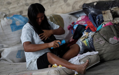 An indigenous Warao woman from Venezuela, combs her hair at a shelter in Pacaraima, Roraima state