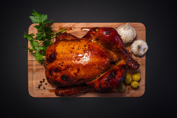 Whole roasted chicken on cutting board with vegetables over black background