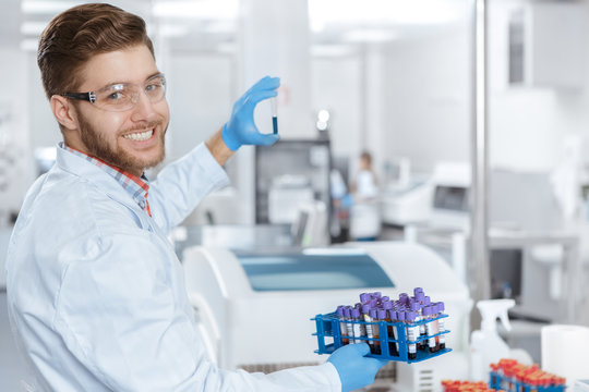 Professional laboratory technician holding a test tube at the laboratory