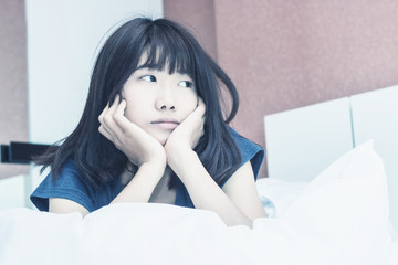 Asian woman wake up on bed in bedroom in the morning.at home in holiday.