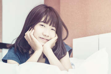 Asian woman wake up on bed in bedroom in the morning.at home in holiday.color tone