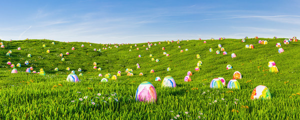Looking for many easter eggs on green meadow as a panorama header