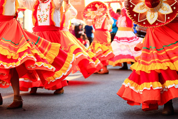 a group of mexican women dancing with bright handmade mexican dresses during mexican carnival Wall mural