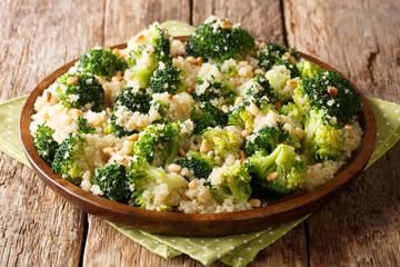 boiled broccoli salad with quinoa and pine nuts closeup on a plate. horizontal