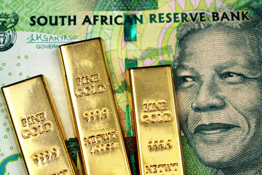 A macro image of a green ten rand note from South Africa with three small gold bars