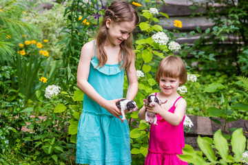 Two sisters stand in the garden and hold in hands 4-days-old Estonian hound puppies. Summertime in countryside.