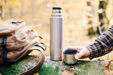Male hand holding cup near the thermos.